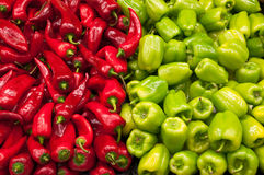 Paprika and Bell Peppers. Horizontal photo from a grocery stand, red paprika and green bell peppers. The frame is vertically divided in two parts royalty free stock photo