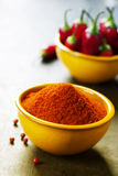 Paprika in a bowl and hot chili peppers Stock Photos