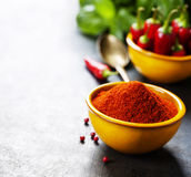 Paprika in a bowl and hot chili peppers Royalty Free Stock Photography