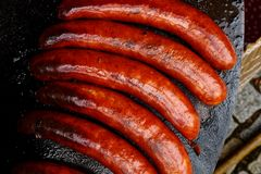 Paprika bratwurst sausages on cast iron griddle from above. Royalty Free Stock Image