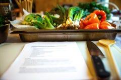 Paprika, cebolla de la primavera, otras verduras en una bandeja y una receta foto de archivo libre de regalías