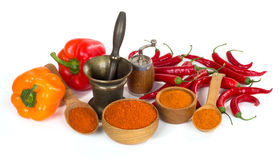 Paprika and chili powder ground in a wooden bowl and spoon on wh Stock Photos