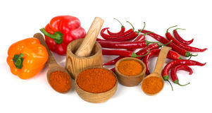 Paprika and chili powder ground in a wooden bowl and spoon on wh Stock Images
