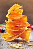 Paprika chips with chili peppers on a wooden background Royalty Free Stock Photography