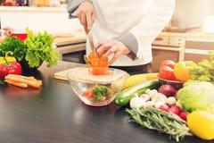 Paprika do corte do cozinheiro chefe para a salada vegetal na cozinha Imagens de Stock Royalty Free