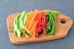 Paprika doce fresca do pepino, da cenoura, a vermelha e a verde cortada nas listras em uma placa de corte de madeira verde-oliva  Fotos de Stock