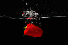 Paprika falling into the water with a splash Stock Images
