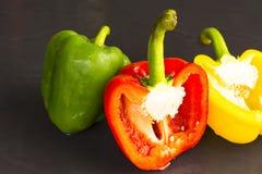 Paprika groen en rood en geel op zwarte achtergrond Ingrediënt van voedsel Stock Afbeeldingen