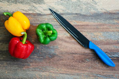 Paprika with a kitchen knife lying on a wooden floor. Paprika, sweet pepper with a kitchen knife on a wooden frame a view of the above elements Stock Images