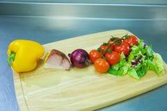 Paprika, lard, oignons, tomates et laitue, se trouvant sur un support en bois photo libre de droits