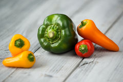Paprika mix, sweet mini red, yellow and orange peppers and green pepper on a wooden background Royalty Free Stock Photo