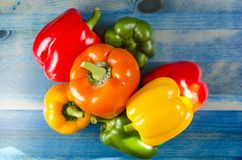 Paprika pepper yellow orange red green close up on blue wooden background. Copy space close-up stock photography
