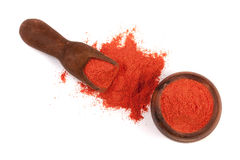 Paprika powder in a wooden bowl with a scoop isolated on white background. Top view.  Stock Images