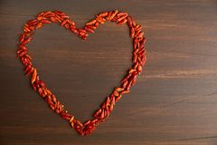 Paprika red pepper in the shape of heart. The texture on a wooden background. Valentine`s Day. Paprika red hot pepper in the shape of heart. The texture on a royalty free stock image