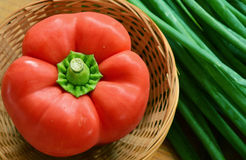 Paprika roja en cesta con las cebollas de la primavera Foto de archivo