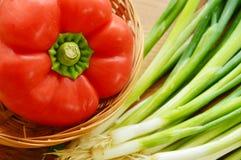 Paprika roja en cesta con las cebollas de la primavera Imágenes de archivo libres de regalías