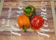 Paprika roja, verde y anaranjada de las pimientas en una tabla mostrada fotografía de archivo