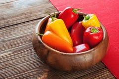 Paprika rojo, anaranjado, amarillo en cuenco de madera en una servilleta roja Foto de archivo