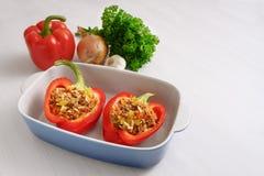 Paprika rojo relleno en una cazuela que cuece azul e ingredientes en una tabla blanca, espacio de la copia fotografía de archivo