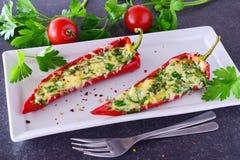 Paprika rouge cuit par four bourré du fromage, de l'ail et des herbes d'un plat blanc avec le parcley et des tomates-cerises Photo libre de droits