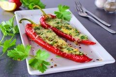 Paprika rouge cuit par four bourré du fromage, de l'ail et des herbes d'un plat blanc avec le parcley et des tomates-cerises Photographie stock libre de droits