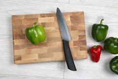 Paprika's met een ceramisch mes op een houten raad Stock Afbeelding