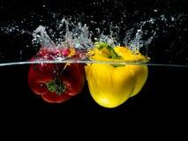 Paprika Splash roja y amarilla en el agua aislada en fondo negro Fotografía de archivo libre de regalías