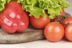 Paprika, tomaten en salade op scherpe raad Stock Fotografie