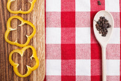 Paprika on utting board. Paprika, allspice in wooden spoon lying on wooden cutting board and checkered tablecloth Royalty Free Stock Photos