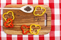 Paprika on utting board. Paprika, allspice in wooden spoon lying on wooden cutting board and checkered tablecloth Stock Images