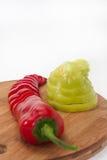 Paprika vermelha e verde desbastada em uma placa de madeira da cozinha Fotos de Stock Royalty Free