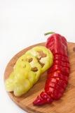 Paprika vermelha e verde desbastada em uma placa de madeira da cozinha Imagem de Stock