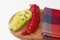Paprika vermelha e verde desbastada em uma placa de madeira da cozinha Fotos de Stock