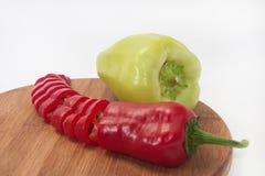 Paprika vermelha e verde desbastada em uma placa de madeira da cozinha Foto de Stock Royalty Free