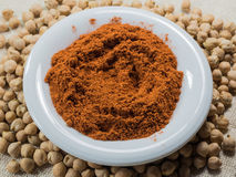 Paprika on a white plate. Ground paprika on a white plate and chickpeas on sacking Stock Image