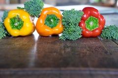 Paprika y bróculi, aún vida de frutas y verduras en fondo de madera Foto de archivo libre de regalías