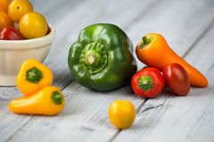 Paprikamischung und -schüssel mit Kirschtomaten, süße mini rote, gelbe und orange Pfeffer und grüner Paprika auf einem hölzernen  Lizenzfreies Stockbild