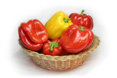 Paprikas in basket. Red and yellow paprikas in basket royalty free stock photos