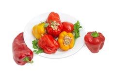 Paprikas bourrés et deux poivrons frais à coté Photos stock