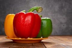 Paprikas colorés frais avec des égouttements sur la table image libre de droits