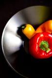 Paprikas colorés frais dans la cuvette sur le fond noir Image stock