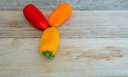 Paprikas coloreados en un fondo de madera resistido Foto de archivo