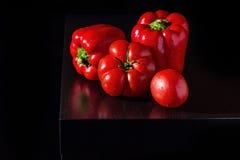 Paprikas de Jucy et tomates fraîches sur le fond en bois foncé Photo stock