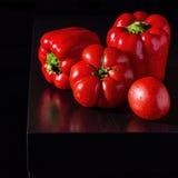 Paprikas de Jucy et tomates fraîches sur le fond en bois foncé Photographie stock