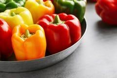 Paprikas doux rouges, verts et jaunes sur la table, Photo stock