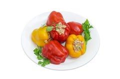 Paprikas et brindilles bourrés de verdure sur le plat blanc Photo stock