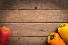 Paprikas rojos de las verduras frescas/anaranjados orgánicos en backgr de madera Fotografía de archivo