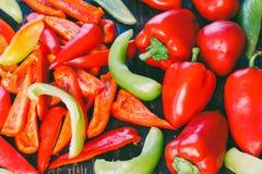 Paprikas rojos y verdes enteros y cortados Fotografía de archivo