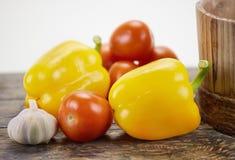 Paprikas, tomates y ajo en la madera Foto de archivo libre de regalías