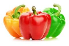 Paprikas verdes, rojas y anaranjadas aisladas en el fondo blanco Foto de archivo